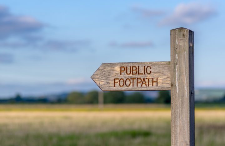 Wooden sign post with public footpath written on it